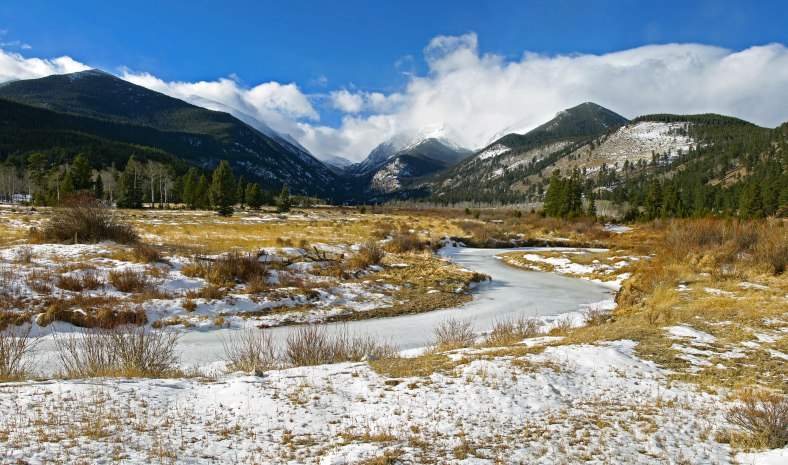 A snow covered valley and frozen Creek in Estes Park