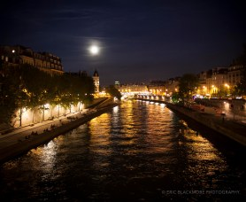 Full moon rising over the Seine at the edge of the blue hour